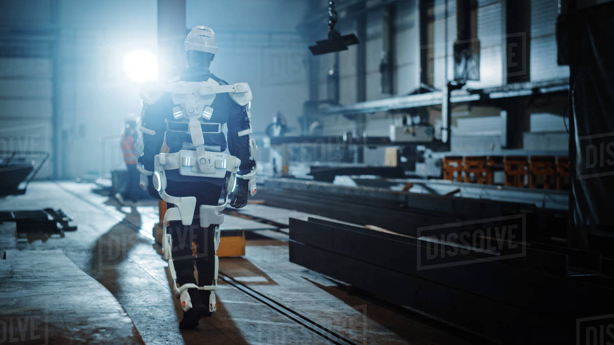 Black African American Engineer is Testing a Futuristic Bionic Exoskeleton and Proudly Wearing it in a Heavy Steel Industry Factory. Successful Contractor Walking in a Powered Mobile Machine Shell. Royalty-free stock photo
