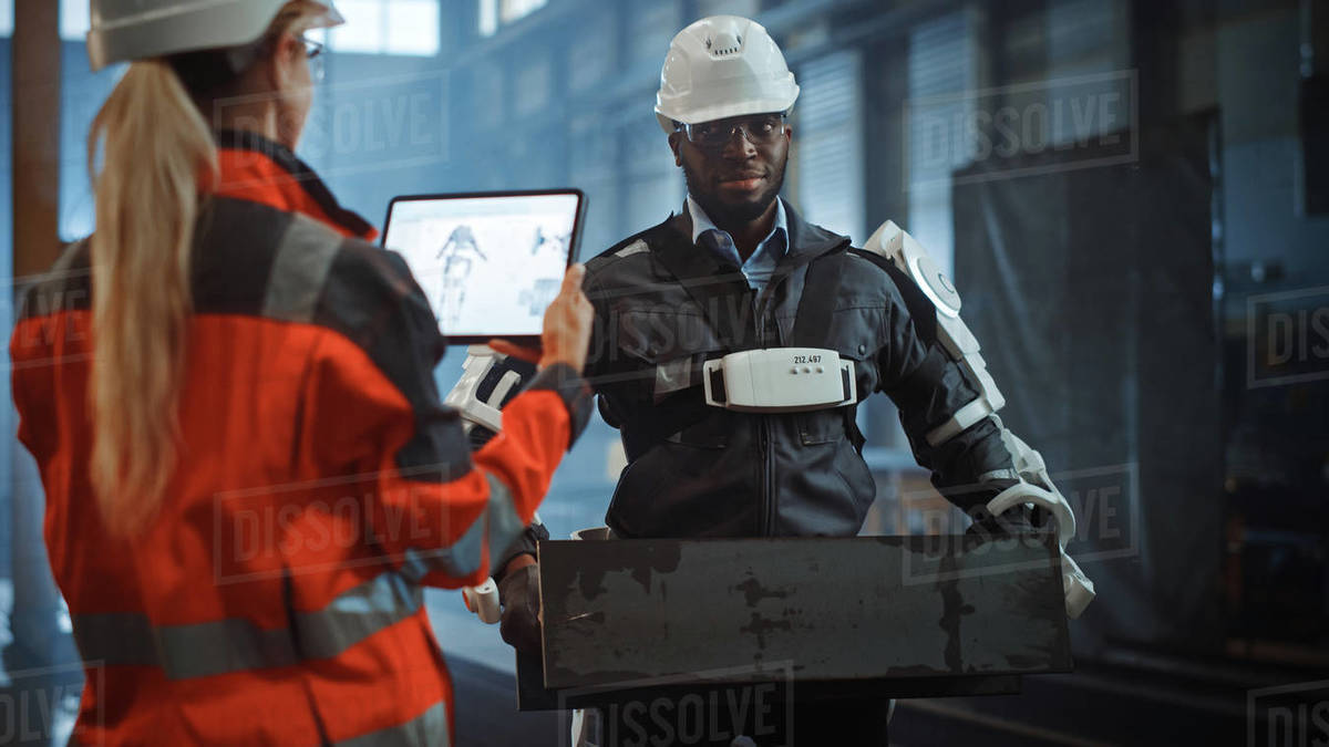 Female Engineer is Testing Vital Components of a Futuristic Bionic Exoskeleton that Her Project Assistant is Wearing in a Metal Industry Factory. Contractor is Lifting Steel Parts in a Powered Shell. Royalty-free stock photo