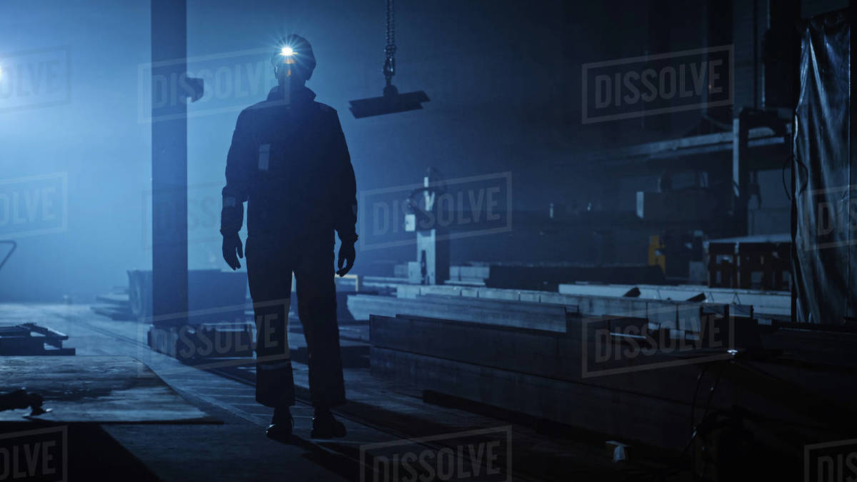 Professional Heavy Industry Engineer/Worker Wearing Uniform, Flashlight on the Hard Hat in a Steel Factory. Industrial Specialist Walking Towards the Camera in a Dark Metal Construction Manufacture. Royalty-free stock photo