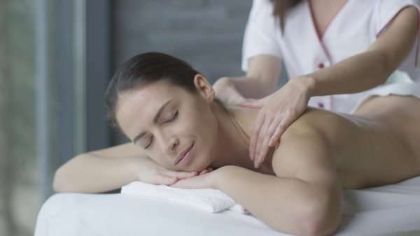 Beautiful woman is getting a relaxing massage from a female masseur in wellness center. Royalty-free stock video