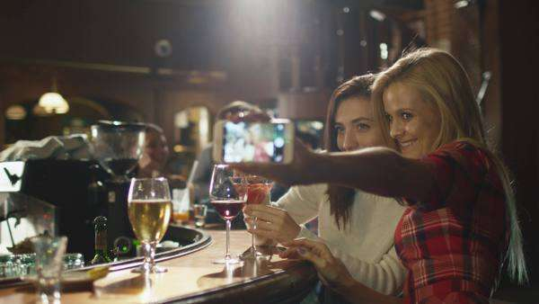 Two beautiful girls are doing selfies on a smartphone while having a good time in a bar. Royalty-free stock video