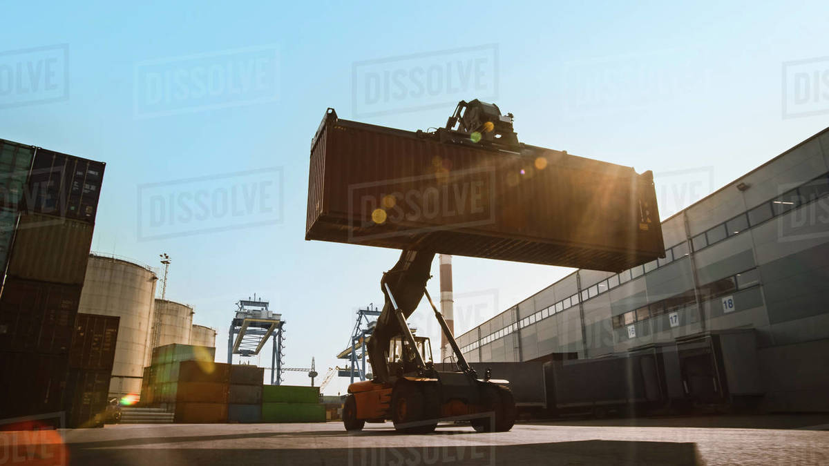Modern Container Handler Carrying a Large Red Steel Shipping Cargo Storage Container in a Shipyard Terminal Royalty-free stock photo