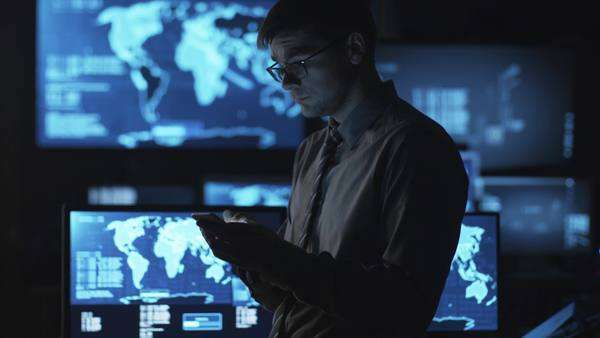 Man in glasses is using a smartphone in a dark monitoring room filled with display screens. Royalty-free stock video