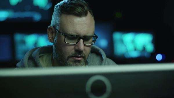 Portrait footage of concentrated male employee working on a computer in a dark office room with display screens with maps and data. Royalty-free stock video