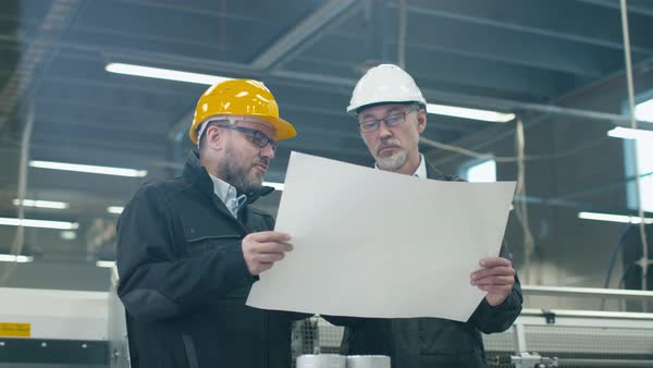 Two engineers in hardhats discuss a blueprint while standing in a factory. Royalty-free stock video