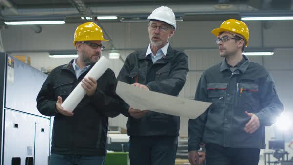 Senior engineer and two workers are walking with papers through the factory space. Royalty-free stock video