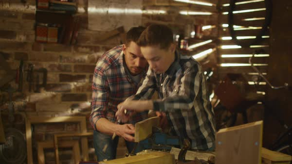 Father and son are woodworking in a garage at home. Royalty-free stock video