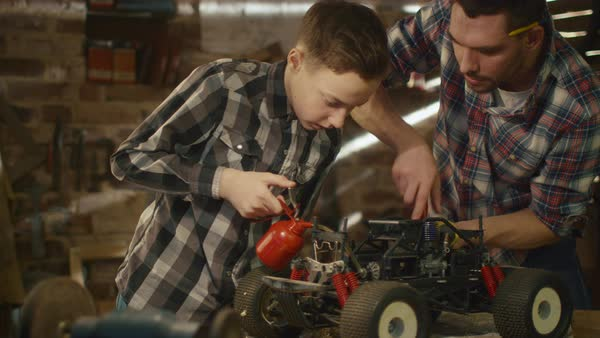Father and son are working on a remote control toy car in a garage at home. Royalty-free stock video
