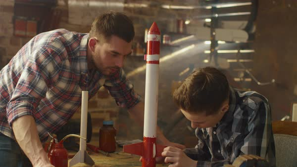 Father and son are modeling a toy rocket in a garage at home. Royalty-free stock video