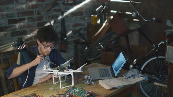 Student is soldering electrical components on a drone in a garage while checking a laptop computer. Royalty-free stock video
