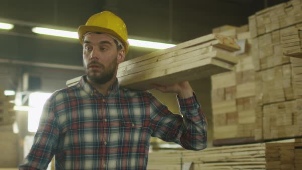 Lumber mill worker in hardhat is carrying wood in warehouse. Royalty-free stock video