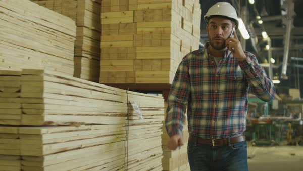 Worker is talking on a mobile phone in lumber factory warehouse. Royalty-free stock video