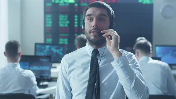 Stockbroker is actively talking using headset at stock exchange. Royalty-free stock video