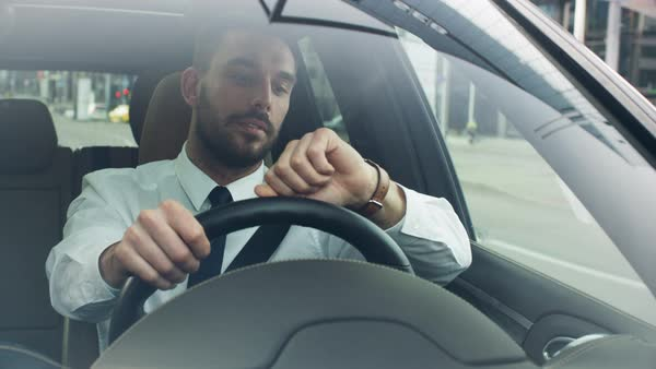 Businessman driving a car in business district, checking the time. Royalty-free stock video
