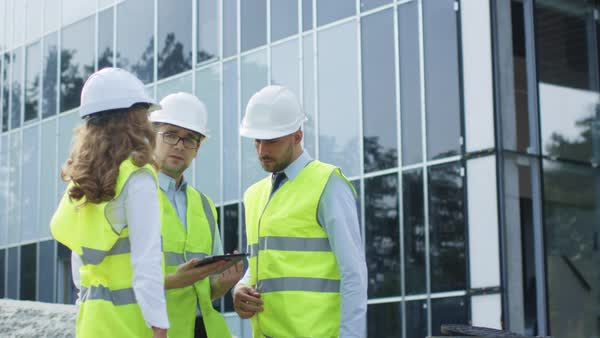 Team of three engineers having conversation and using tablet computer, glass building under construction in background. Royalty-free stock video
