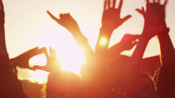 Group of people dancing and raising hands outdoors in sunlight. Royalty-free stock video