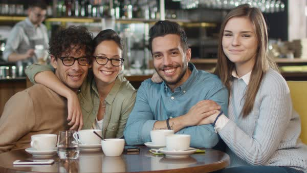 Group of young smiling people looking at camera and waving with hands in coffee shop. Royalty-free stock video