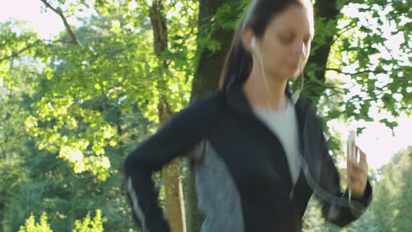 Young Woman Using Mobile Phone While Running Outdoors. Royalty-free stock video