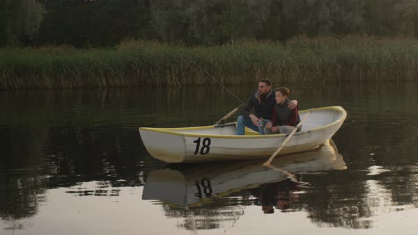 Father and son are sitting in the boat and fishing Royalty-free stock video