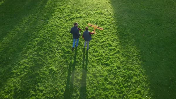 Father and son running in the field with model airplane, aerial shot Royalty-free stock video