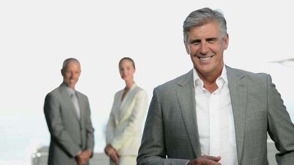 Mature businessman presenting facing camera with business people moving in background. Royalty-free stock video