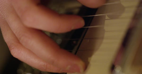Hand-held shot of fingers picking guitar strings Royalty-free stock video
