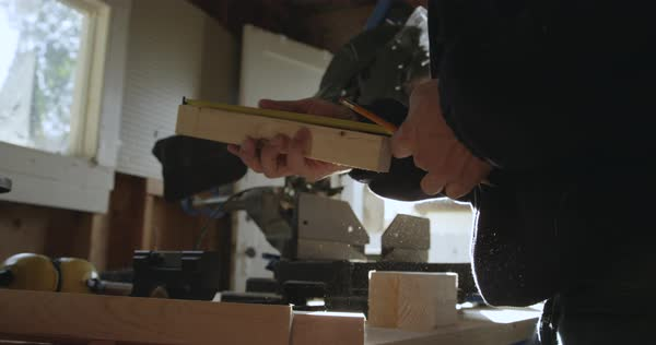 Hand-held shot of a carpenter measuring a piece of wood with a tape Royalty-free stock video