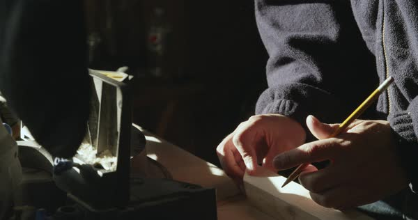 Hand-held shot of a carpenter measuring and marking a piece of wood Royalty-free stock video