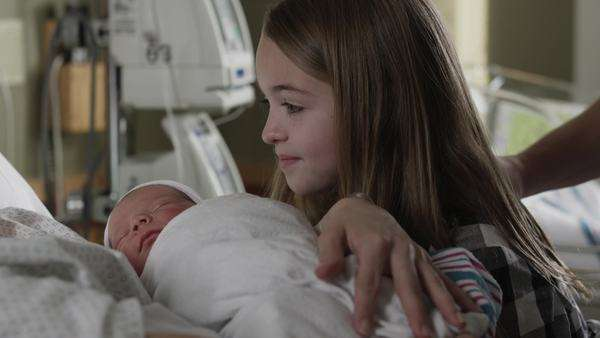 Close-up mother and sister (8-9) looking at newborn baby (0-1 months) in hospital / Payson, Utah, USA Rights-managed stock video