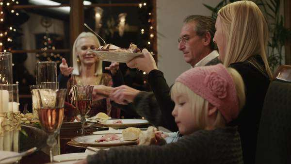 Medium shot dolly shot pan family with children (2-5 months, 2-9 years) having Christmas dinner / Cedar Hills, Utah, USA Rights-managed stock video