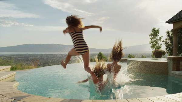 panning slow motion medium shot of girls running and jumping into infinity pool cedar hills united states l64 infinity