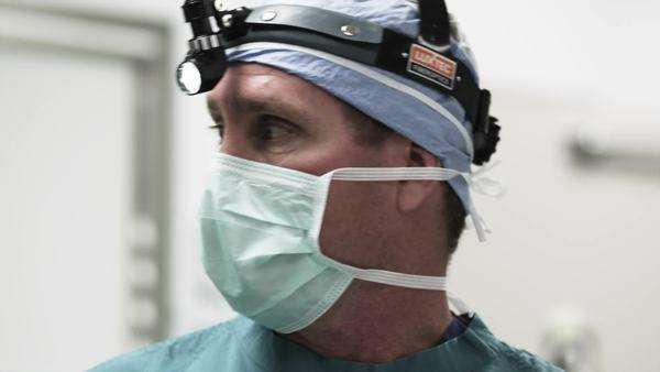 Close-up tilt of TD Male doctor with light on head in operating room Royalty-free stock video
