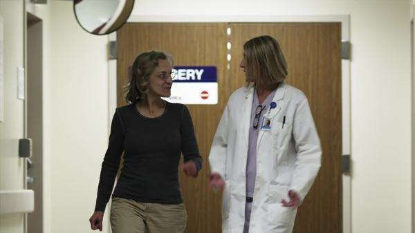 Medium shot of doctor and friend talking in hospital corridor Royalty-free stock video