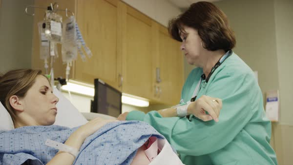 Medium panning shot of nurse checking vital signs of pregnant patient Rights-managed stock video