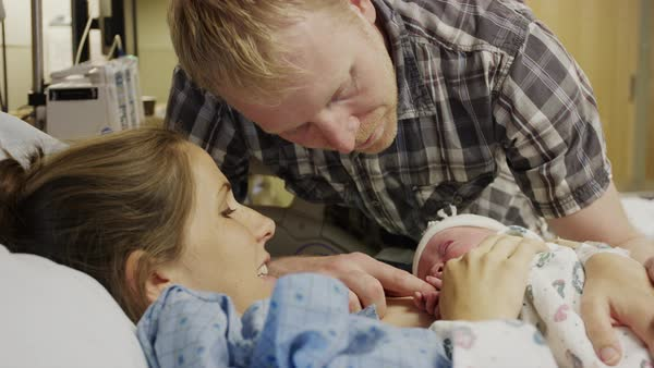 Close up shot of parents admiring newborn baby in hospital Rights-managed stock video