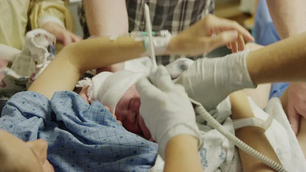 Close up high angle view of doctor checking temperature of newborn baby Rights-managed stock video
