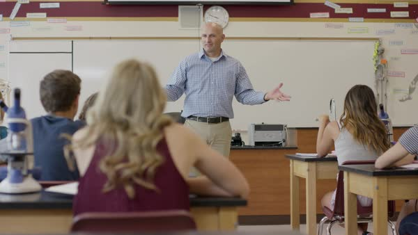Medium panning shot of teacher lecture high school science class Rights-managed stock video