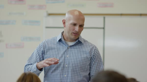 Medium panning shot of teacher talking in high school classroom Rights-managed stock video