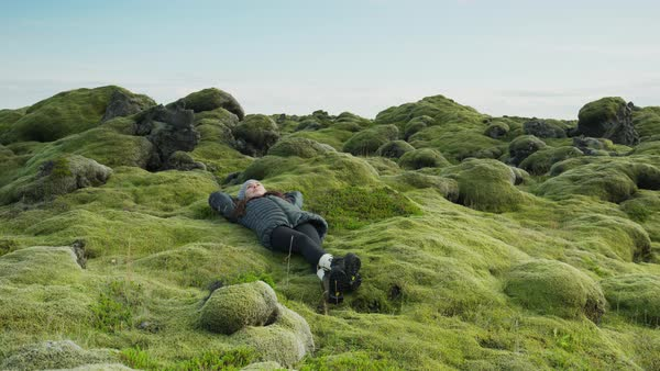 Wide panning shot of woman laying in mossy landscape Rights-managed stock video