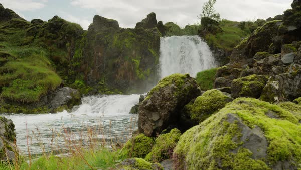 Wide panning shot of flowing waterfall near rocks Royalty-free stock video