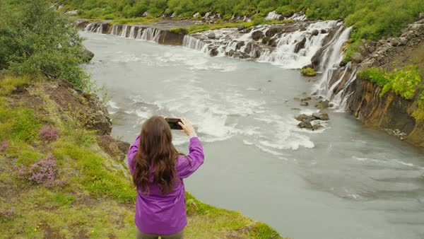 Wide high angle crane shot of woman photographing waterfalls Royalty-free stock video