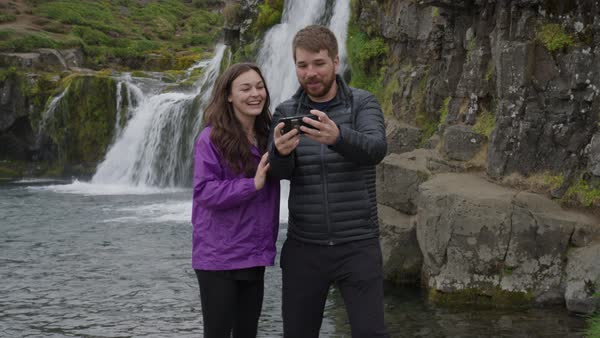 Medium shot of couple posing for cell phone selfie near waterfalls Royalty-free stock video