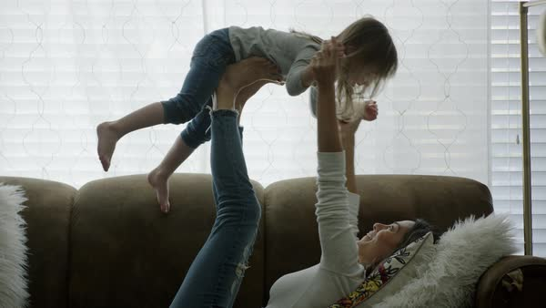 Medium shot of mother and daughter playing on sofa Royalty-free stock video