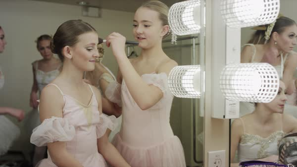 Medium shot of ballerinas applying makeup in dressing room mirror Rights-managed stock video