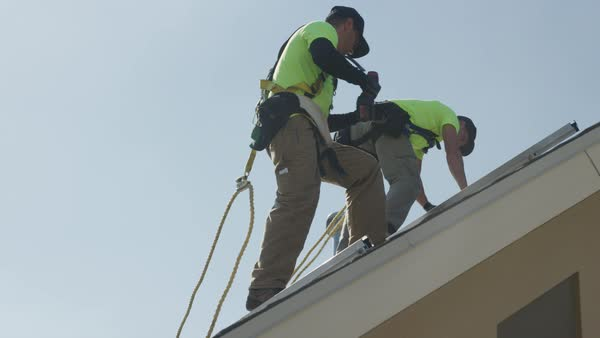 Medium panning low angle shot of workers installing rails on roof Royalty-free stock video