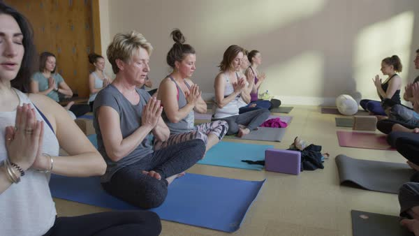 Medium zoom in shot of yoga class in prayer pose Royalty-free stock video