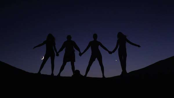 Medium shot of silhouetted friends holding hands on hill against night sky, Lake Powell, Utah Royalty-free stock video