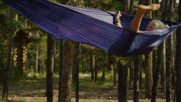 Medium shot of girl spinning in hammock in forest, Idaho Royalty-free stock video