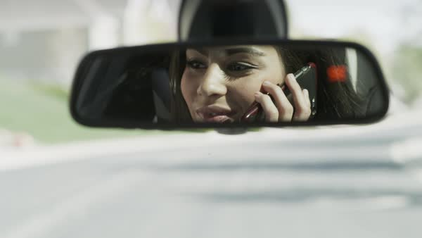 Close up of woman talking on cell phone in car mirror Royalty-free stock video