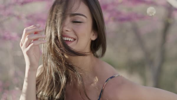 Close up portrait of smiling woman tossing hair near flowering trees Royalty-free stock video